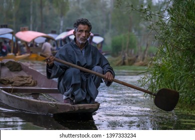 Srinagar, Jammu and Kashmir - April 16, 2019 : Kashmiri men old wooden boat rowing to floating market on Dal Lake daily early morning is major tourist attractions in Srinagar