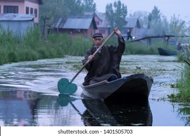 Srinagar, Jammu and Kashmir - April 16, 2019 : Kashmiri men old wooden boat rowing to floating market on Dal Lake daily early morning is major tourist attractions in Srinagar, Kashmir, India