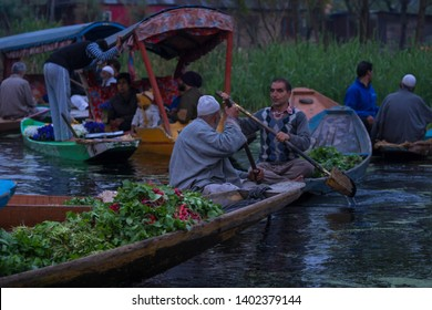 Srinagar, Jammu and Kashmir - April 16, 2019 : Kashmiri men Indian vegetable traders at floating market on Dal Lake daily early morning is major tourist attractions in Srinagar, Kashmir, India