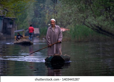Srinagar, Jammu and Kashmir - April 16, 2019 : Kashmiri men with old wooden boat rowing to floating market on Dal Lake daily early morning is major tourist attractions in Srinagar, Kashmir, India
