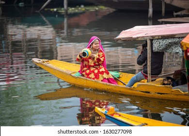 Srinagar, Jammu and Kashmir - April 16, 2019: Kashmiri photographer taking pictures pre wedding of  young woman in Indian bridal dresses on wooden boat at Dal Lake, Kashmir, India