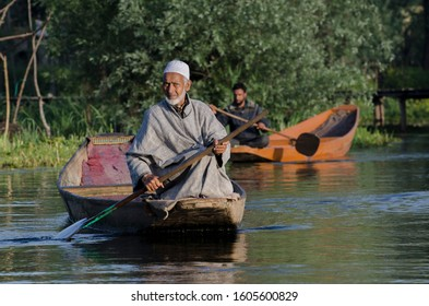Srinagar, Jammu and Kashmir - April 2018: an elderly muslim man rowing a dingy or a local boat called shikara  in the dal lake selling vegetables in the floating market .