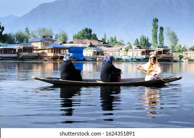 Srinagar, Jammu and Kashmir - April 2018: A kashmiri woman rowing a boat carrying two other muslim women in burkha in the dal lake of srinagar.