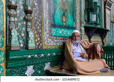 SRINAGAR, JAMMU AND KASHMIR, INDIA - 20 JUNE 2017: Muslim Imam welcoming faithful before the entry to a green uniquely wooden mosque, Shah E Hamdan