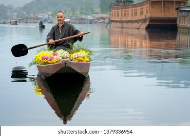 Srinagar, Jammu and Kashmir, India - April 16, 2019 : Kashmiri merchants old wooden boat paddle for selling flowers to tourists in Dal Lake, at Houseboat the famous place of travel destination