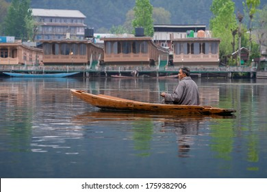 Srinagar, Jammu and Kashmir, India - April 16, 2019 : Kashmiri man rowing wooden boat who lives in the Dal Lake is the famous place of travel destination in Srinagar India