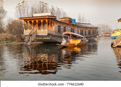Srinagar, Jammu and Kashmir, India - November 19, 2015 : A shikara boat passing by a large houseboat at Dal lake in srinagar, Jammu and Kashmir, Indiia