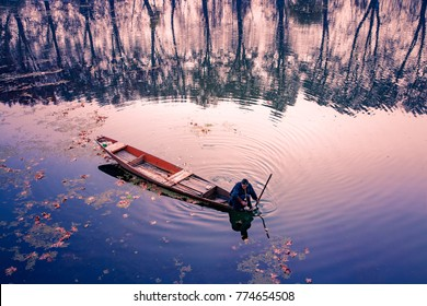 Srinagar, Jammu and Kashmir, India - November 16, 2015 : A Kashmiri man smoking hukkah in his canoe on Dal Lake at Srinagar, Jammu and Kashmir, India