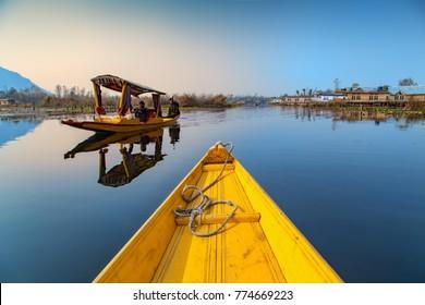 Srinagar, Jammu and Kashmir, India - November 16, 2015 : Two Shikara Tourist Boats passing each other at Dal lake in Srinagar, Jammu and Kashmir, India