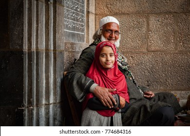 Srinagar, Jammu and Kashmir, India - November 16, 2015 : A smiling cleric with a girl child outside mosque, Jamia Masjid, Srinagar, Jammu and Kashmir, India