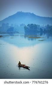 Srinagar, Jammu and Kashmir, India - November 15, 2015 : A Kashmiri man rowing his canoe, also seen a fort on a hill-top at Nageen Lake in Srinagar.