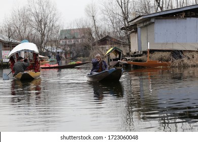Srinagar, Jammu and Kashmir - March 16, 2019 : Kashmiri men old wooden boat rowing to floating market on Dal Lake daily early morning is major tourist attractions in Srinagar, Kashmir, India