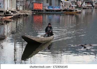 Srinagar, Jammu and Kashmir - March 18, 2019 : Kashmiri men with old wooden boat rowing to floating market on Dal Lake daily early morning is major tourist attractions in Srinagar, Kashmir, India
