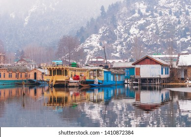 Srinagar, Jammu and Kashmir/India – January 26 2012: Houseboats on theDal Lake on the background of a snow-covered mountain, Srinagar.
