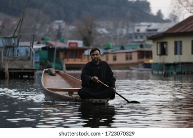 Srinagar, Jammu and Kashmir/India – March 19,2019: A man in a small green traditional wooden boat on the Dal lake.