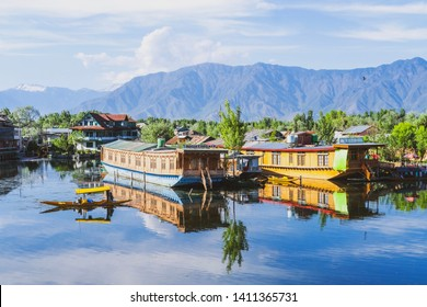SRINAGAR, JAMMU AND KASHMIR/INDIA - MAY 6 2019: View of Dal Lake with house boats and shikaras on it and Himalayas in the background