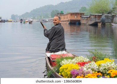 Srinagar, Kashmir, India - April 15, 2019 : Kashmiri merchants with old wooden boat paddle for selling flowers to tourists in Dal Lake, at Houseboat is the famous place travel destination in Srinagar