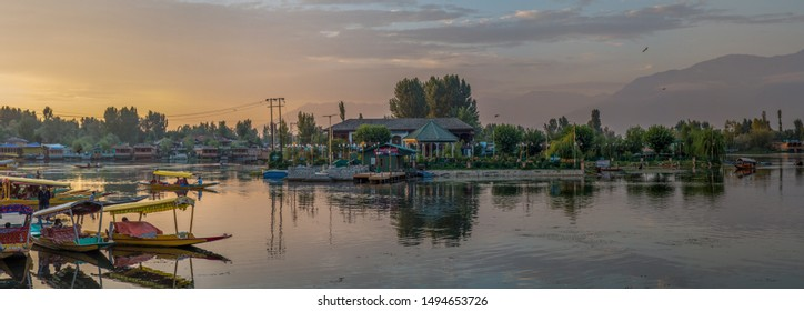 Srinagar, Kashmir / India - August 28 2019: Sunset over Dal Lake with shikaras and houseboats and hotels in the background.