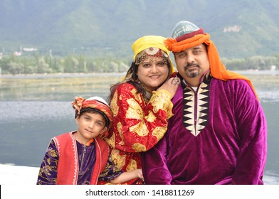 Srinagar, Kashmir, India - Jul 26 2015: Typical Kashmiri attire worn by a family. The background is that is Dal lake in Srinagar, Kashmir. The bright colors bring out happiness.