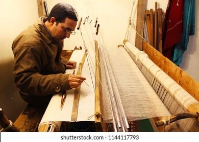 SRINAGAR, KASHMIR, INDIA - MARCH 16 2016: A weaver making Pashmina carpet in Srinagar, Jammu and Kashmir. Pashmina is a native weaving craft of Kashmir and requires highly-skilled weavers.