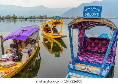 Srinagar,10 April ,2016 : Close up of  boat selling fabrics in Dal Lake with tourist shikaras and  mountains in background.Famous destination for holidays,Kashmir, India , Asia