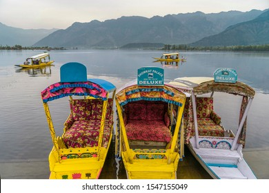 Srinagar,10 April ,2016 : Colorful  shikara boats parked for tourists in Dal Lake with mountains in background. Famous destination for tourists, Kashmir , India ,Asia