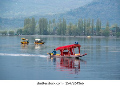 Srinagar,10 April ,2016 :  Engine fitted    decorated red shikara speeding away  in blue waters of Dal Lake with greenery and  mountains in background. Kashmir, India ,Asia