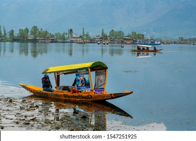 Srinagar,10 April ,2016 : Kashmiri  shikara  boatman  advertising photography service on his boat in Dal Lake with mountain and houseboats   in background ,Kashmir,India ,Asia