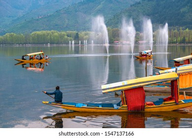 Srinagar,10 April ,2016 :  Tourists enjoying colorful shikara boat ride and view of water fountains in Dal Lake with mountains in background ,Kashmir, India ,Asia