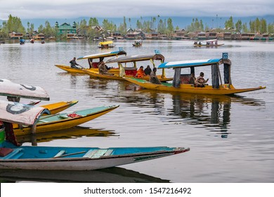 Srinagar,12, April,2016:People enjoy  boating by peddling  Shikaras  on the waters of Dal Lake with mountains in background .Famous destination   for tourists, Kashmir, India ,Asia