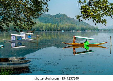 Srinagar,13, April ,2016 : Shikara boats parked in the calm waters of Dal Lake with reflection of mountains in background.  Kashmir, India ,Asia