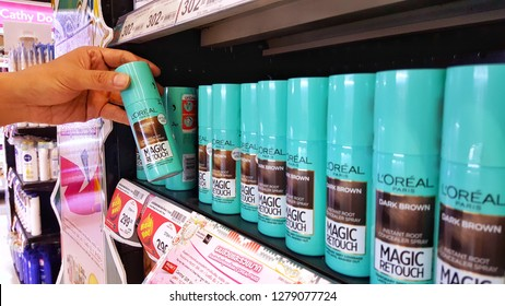 Sriracha, Chonburi THAILAND Dec 18, 2018: Man's hand is holding loreal magic hair retouch bottle from supermarket shelf
