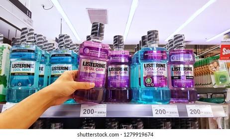 Sriracha, Chonburi THAILAND Dec 18, 2018: Man's hand is holding Listerine mouthwash bottle from supermarket shelf