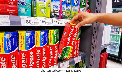 Sriracha, Chonburi THAILAND Dec 18, 2018: Man's hand is holding colgate toothpaste box from supermarket shelf