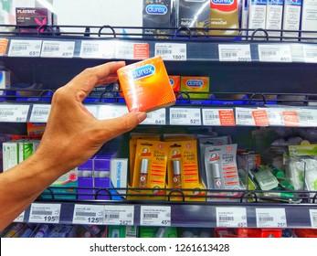 Sriracha, Chonburi THAILAND Nov  16, 2018: Man's hand is holding durex condom box from supermarket shelf.