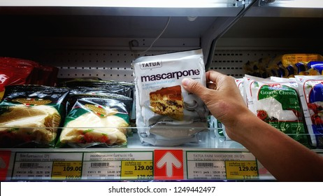 Sriracha, Chonburi THAILAND Nov 25, 2018: Man hand holding a pack of mascarpone cheese display from supermarket shelf. Top view for business or marketing concept.