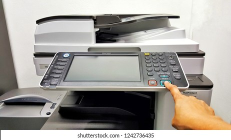 Sriracha, Chonburi THAILAND Nov  5, 2018: Woman's hand press start button on panel of copier at office. Asian woman working in white operating copier on white office background.