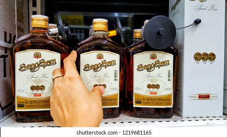 Sriracha, Chonburi THAILAND Oct  23, 2018: Man's hand is holding  thai whisky bottle brand Sangsom from supermarket shelf.