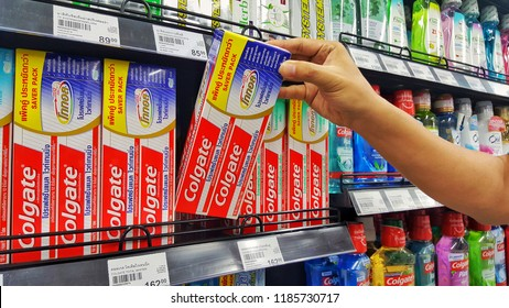 Sriracha, Chonburi THAILAND Sep  18, 2018: Man's hands are holding toothpaste to buy brand Colgate. stacked on a shelf in a supermarket.