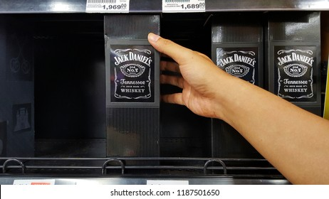 "Sriracha, Chonburi THAILAND Sep  18, 2018: Man's hands are holding whisky bottle  (Brand ""Jack daniel"")  stacked on a shelf in a supermarket."