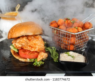 Sriracha Honey Fried Chicken sandwich served with a side of sweet potato tater tots alongside a smoking sweet cocktail
