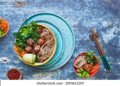 Sriracha meatballs with buckwheat soba noodles, fresh vegetables and herbs. Asian  salad for lunch or dinner. Top view, blank space, rustic background