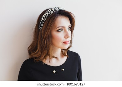 sropped headshot portrait of a brunette with professional make up and hairstyle with hairband accessory,  wearing black dress. Photo taken with  high angle. White wall background