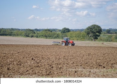 St Albans England UK 1/09/2020 A red Massey Ferguson 6715S 4x4 MFWD 4WD tractor ploughing arable land in the English countryside on an Autumn day