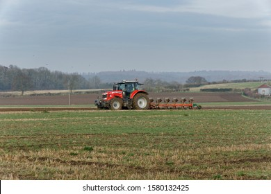 St Albans England UK 5/12/2019 A red Massey Ferguson 7620 tractor ploughing arable land in the English countryside on a winter's day
