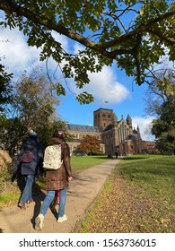 ST ALBANS, UK - 18 NOV 2019: People walk up a hill towards the abbey on a sunny Autumn day
