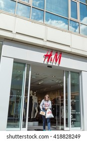 ST ALBANS, UK - MAY 3, 2016: Woman shopper exits H&M clothing store in The Maltings shopping arcade