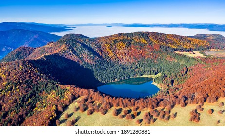 St. Ana's lake, Transylvania, Romania. Stunning autumn scenery with colorful forest and idyllic volcanic lake a popular touristic and travel destination in Europe.