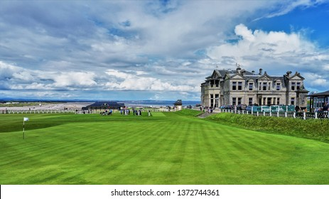 St. Andrews, Scotland - Aug 2017: 18th Hole at St. Andrews historic golf course with member club house in the distance and vibrant clouds in deep blue sky.