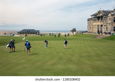 St Andrews, Scotland - May 21, 2018: Man putting a ball at 18 th hole near famous clubhouse golf course St Andrews in Scotland